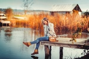 glamourous portrait of the young beautiful woman in leather boots on the bank of a lake on wooden pier